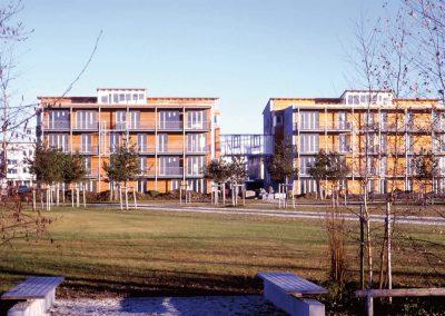 Wohnanlage mit 28 Wohneinheiten in München, Messestadt Riem; Bauherr: WOGENO München e.G. – Genossenschaft für selbstverwaltetes, soziales und ökologisches Wohnen. Das Ziel des Bauvorhabens war u.a. die Versorgung mit dauerhaft preisgünstigem Wohnraum und ein gemeinschaftsorientiertes, nachbarschaftliches Zusammenleben verschiedener Alters-und Einkommensgruppen. Das Objekt hat einen von 18 Ehrenpreisen für guten Wohnungsbau im Jahr 2005 erhalten.
